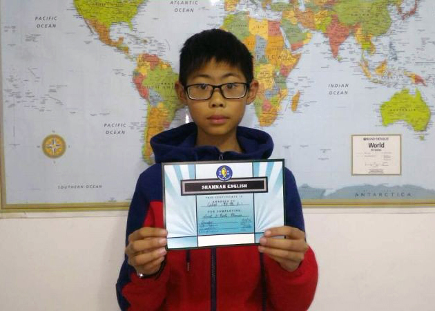 A boy holding up his certificate for completing an english course.