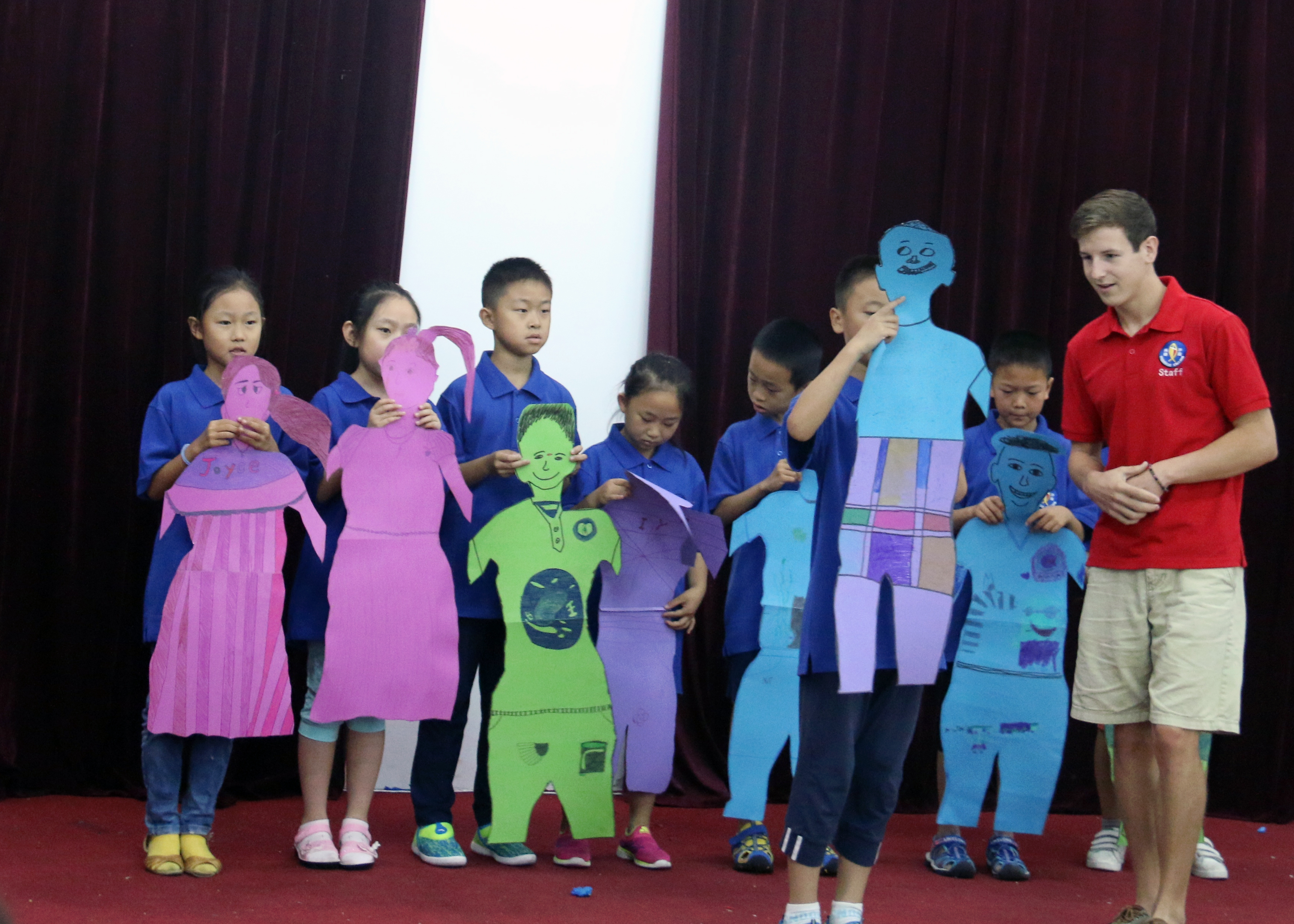 Children showing cut outs of themselves at camp.
